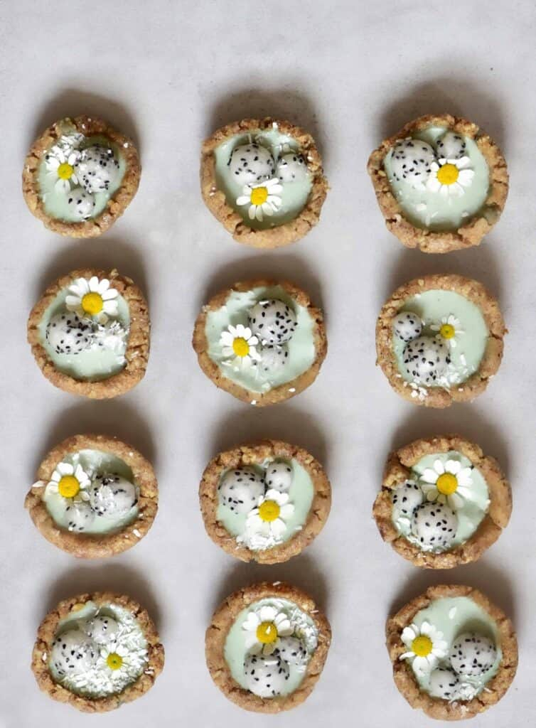 Mini green tarts with dragonfruit balls, coconut, and daisy flowers