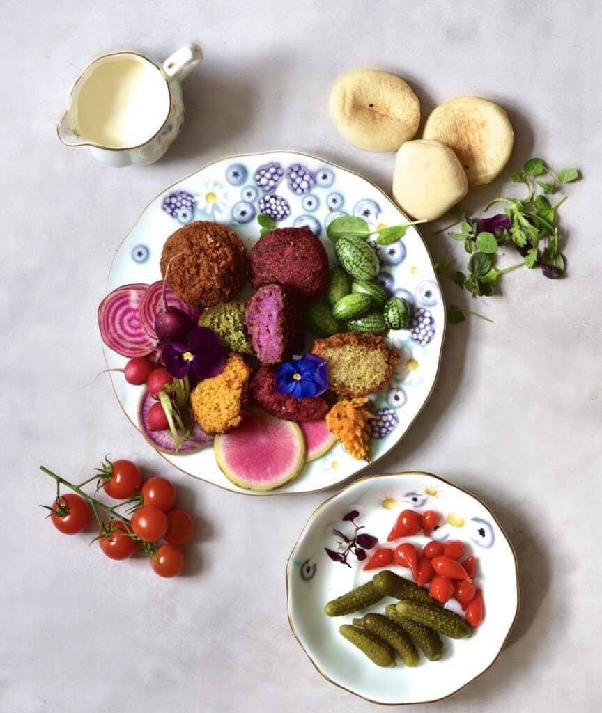Rainbow falafel with veggies, yogurt tahini dip, pita bread and edible flowers