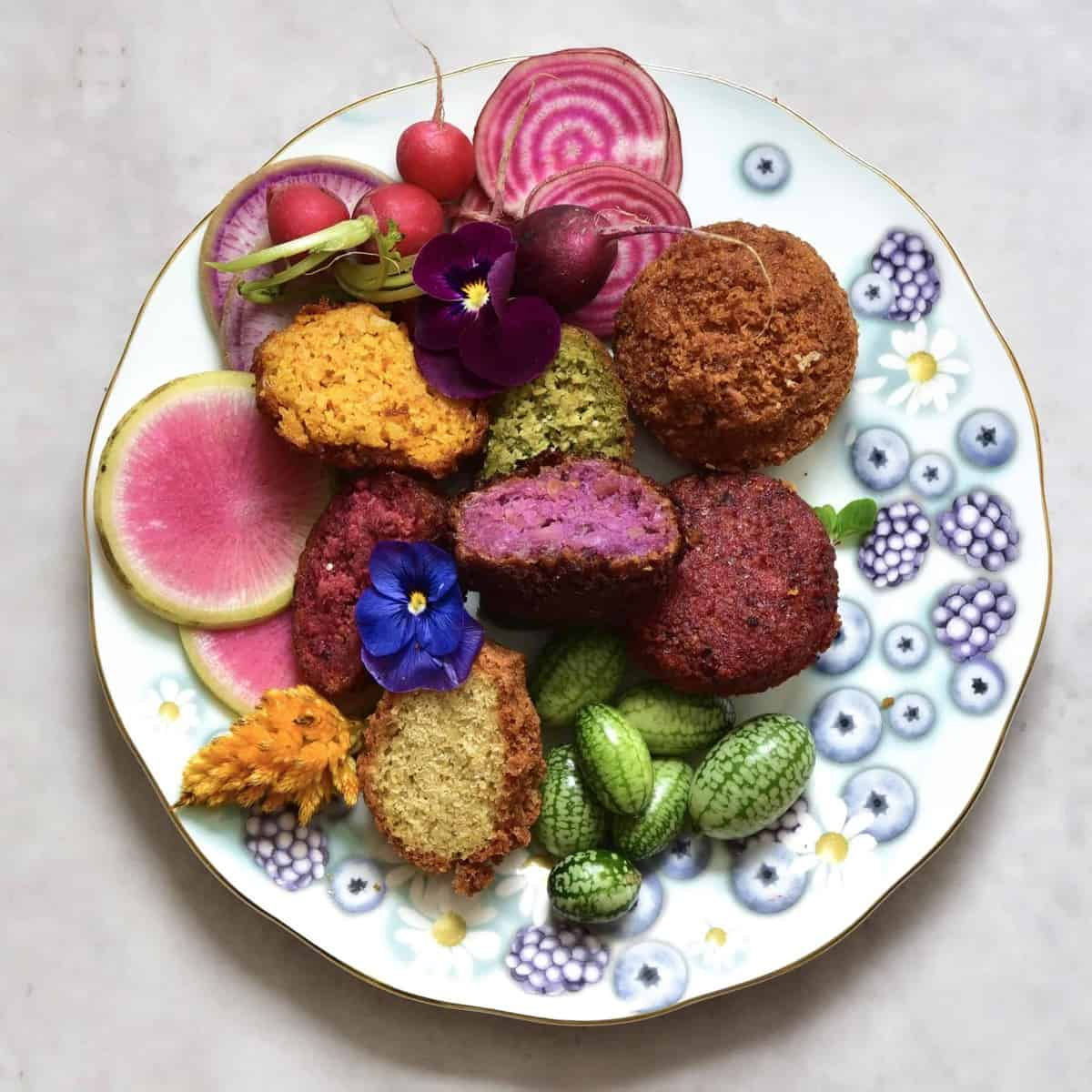 Rainbow falafel with veggies and edible flowers as part of a mezze platter