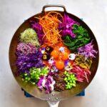 Rainbow veggies and egg yolks on top of rice for a homemade bibimbap