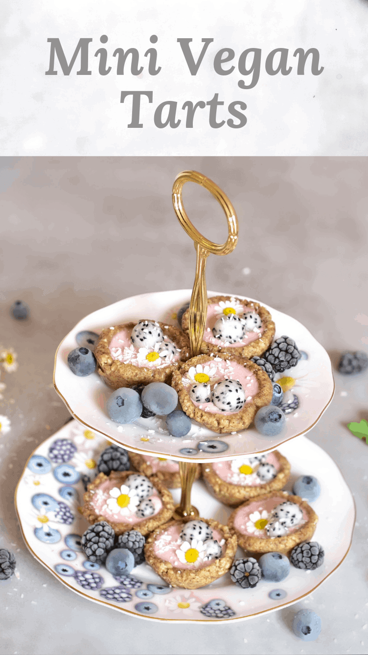 mini vegan tarts with a raspberry-rose filling and topped with frozen berries, edible flower and coconut