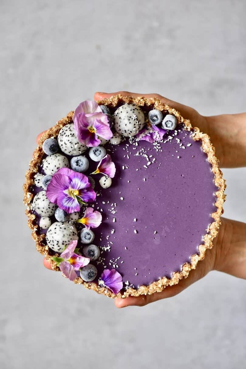 healthy no-bake, refined sugar free, raw vegan earl grey blueberry tart topped with dragon fruit and edible flowers