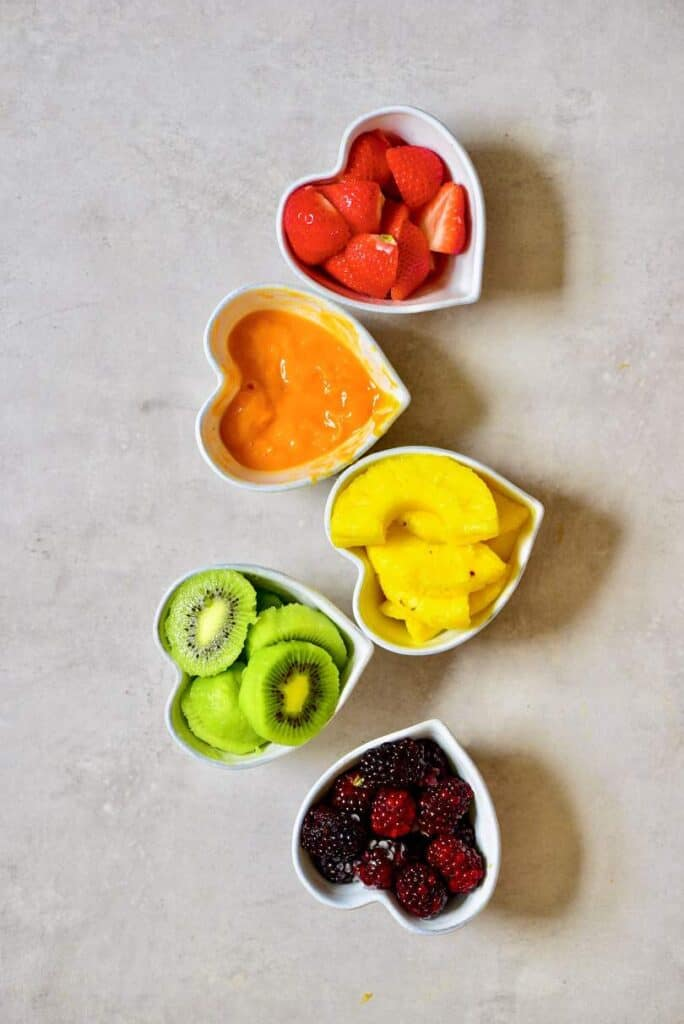 Five bowls filled with strawberries mango pineapple kiwi and blackberries