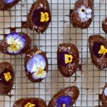 Dates covered with melted chocolate and edible flowers over a cooling rack