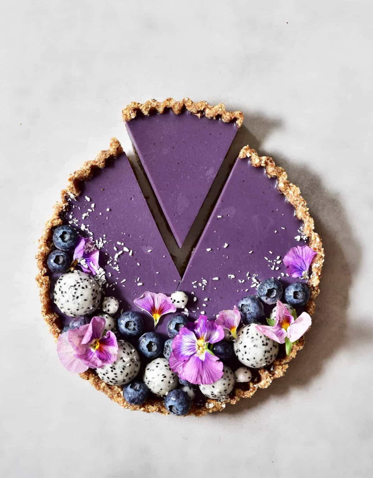 Blueberry tart decorated with blueberries dragon fruit balls and edible flowers with a slice cut off