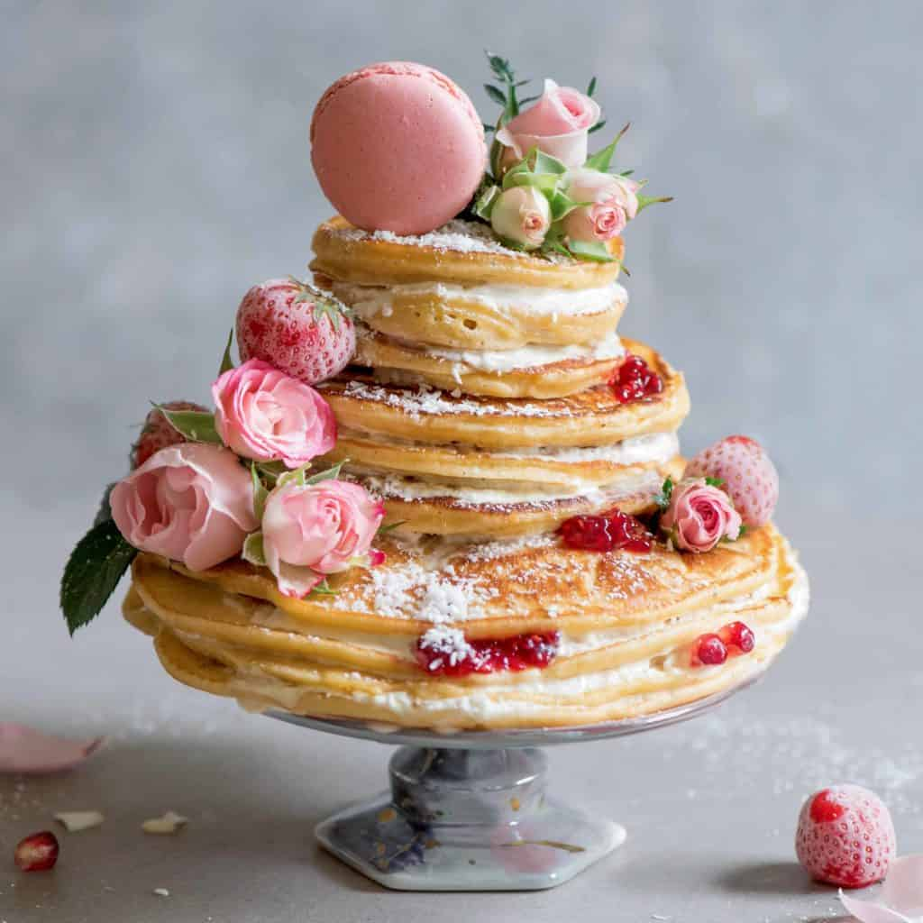 A pancake layered cake decorated with edible roses berries a pink macaroon and shredded coconut