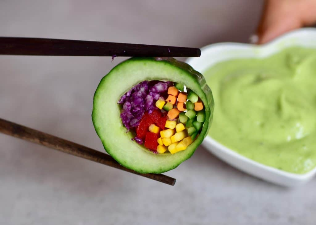Cucumber sushi slice and avocado dip behind it