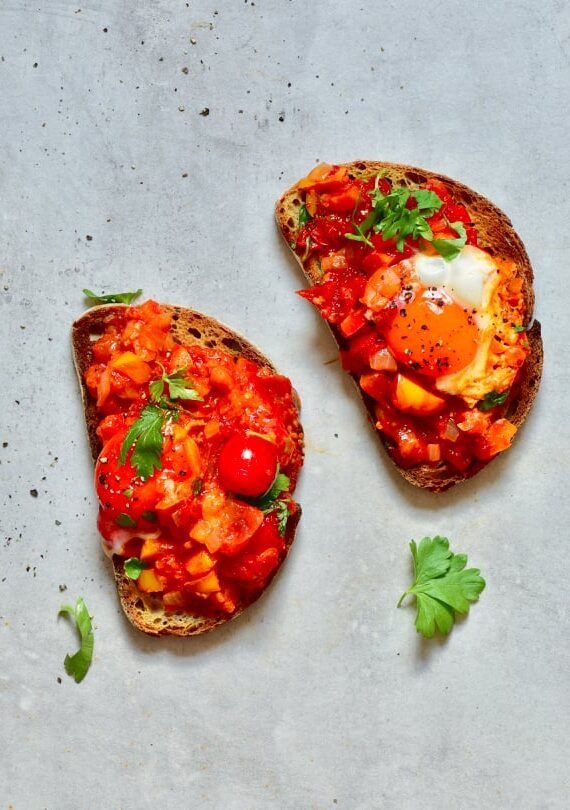 two slices of bread with shakshuka on top