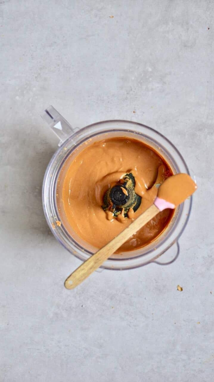 A blender with peanut butter and a spatula put on top of it