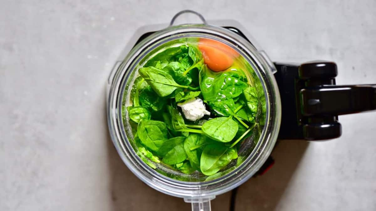 A blender with spinach leaves and an egg