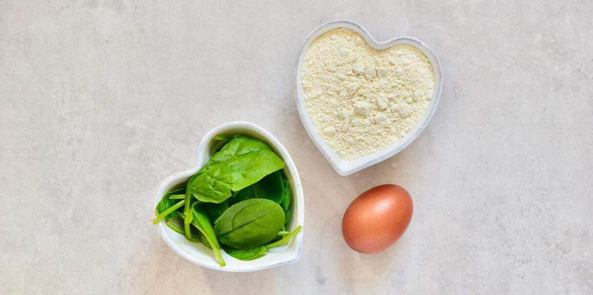 A heart shaped bowl with flour another hear shaped bowl with spinach leaves and an egg on a flat surface