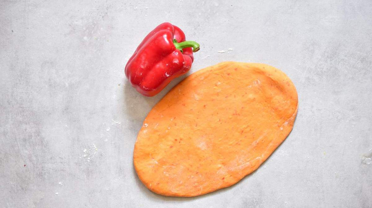 Orange pasta dough with a red pepper on a flat gray surface