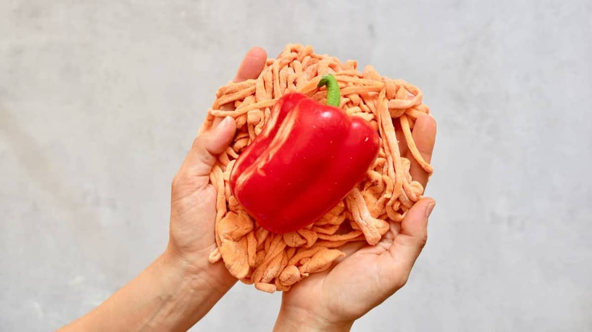 Homemade orange pasta strings with red pepper being held in hands