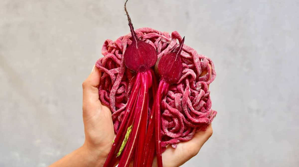 Homemade red pasta strings with beetroot halves being held in hands
