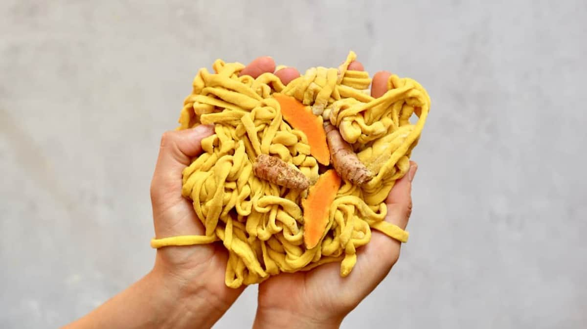 Homemade yellow pasta strings with turmeric halves being held in hands