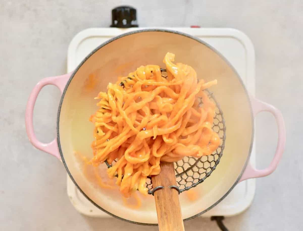 Homemade orange pasta in a colander spoon above a pot