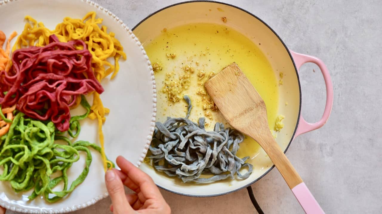 sauteing homemade rainbow pasta in garlic and olive oil dressing