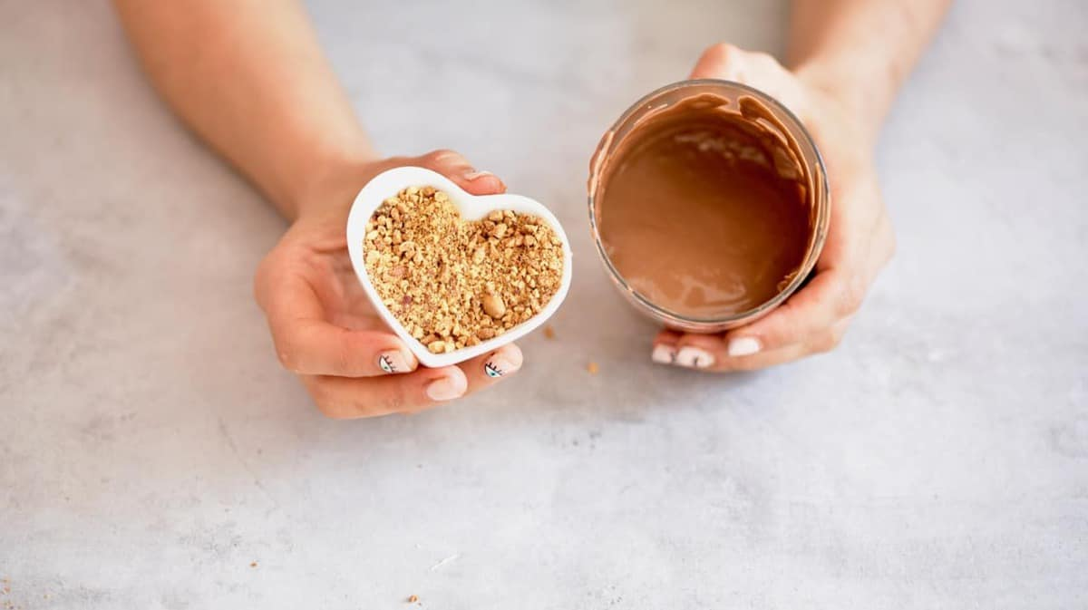 A small hear shaped bowl with peanut crumbs and a glass with melted milk chocolate