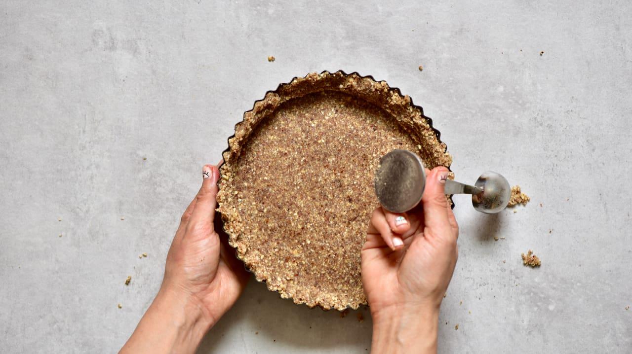 pressing tart crust into tin