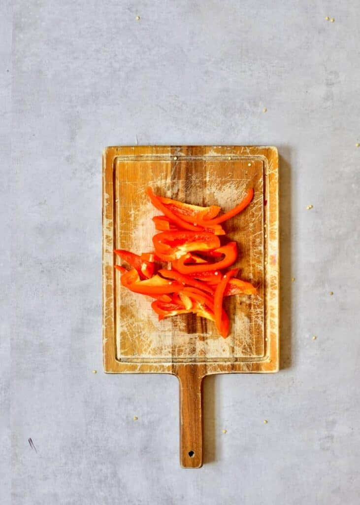 Sliced orange pepper on a wooden board