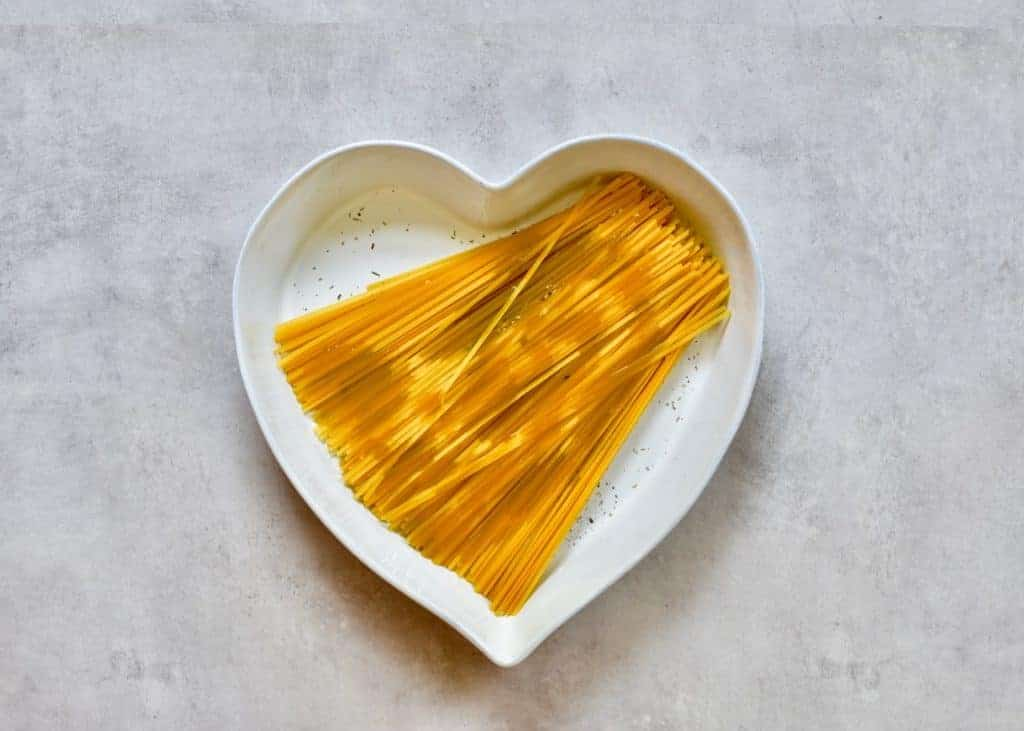 Oil poured over Linguine pasta in a heart shaped dish