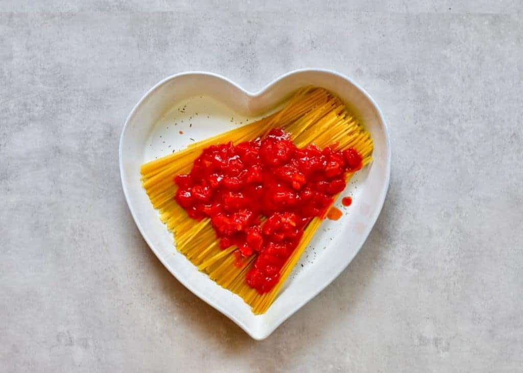 Tomato sauce added over Linguine pasta in a heart shaped dish