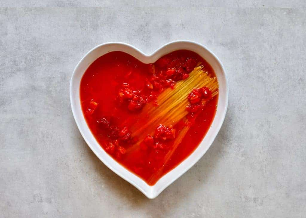 Water added to tomato sauce and Linguine pasta in a heart shaped dish