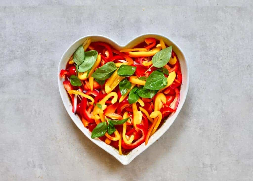 Chopped veggies added to Linguine pasta in a heart shaped dish