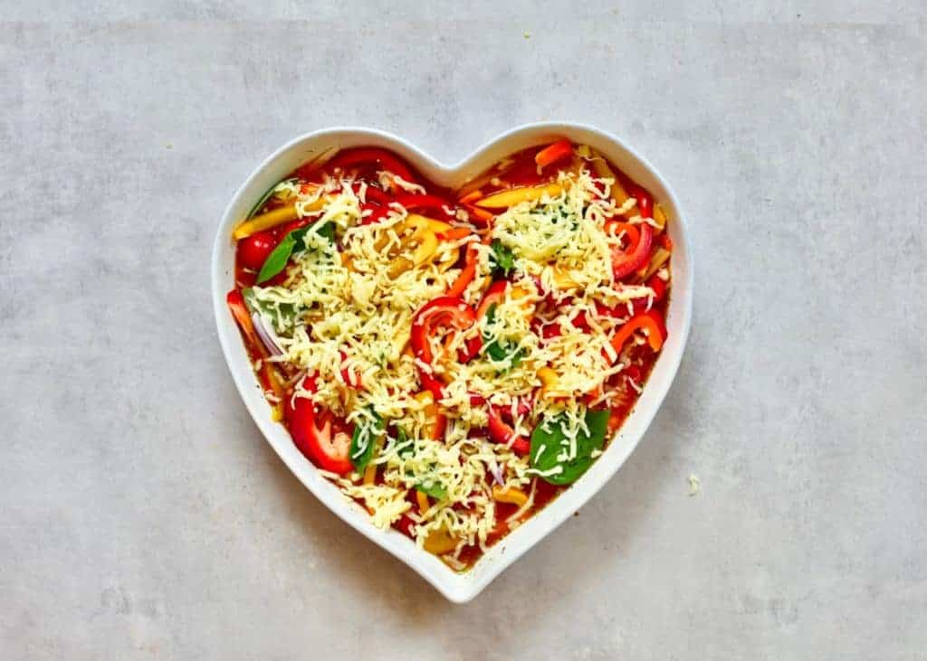 Linguine pasta topped with cheese in a heart shaped dish