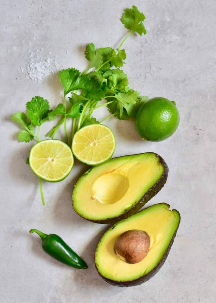 Avocado cut in half, a lime cut in half, a whole lime parsley and a green chili