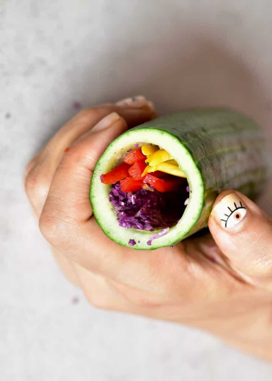 Filling up a cored cucumber with rainbow julienned veggies