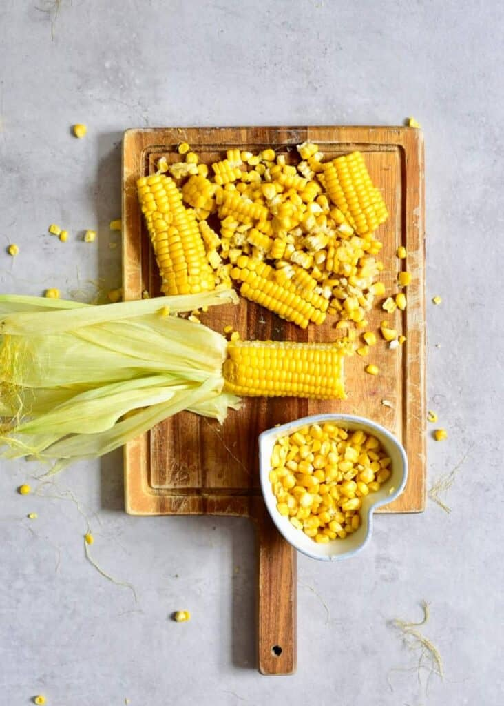 chopped corn on the cub on a wooden chopping board