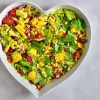 A big heart-shaped bowl filled with corn mango tomato and avocado salad