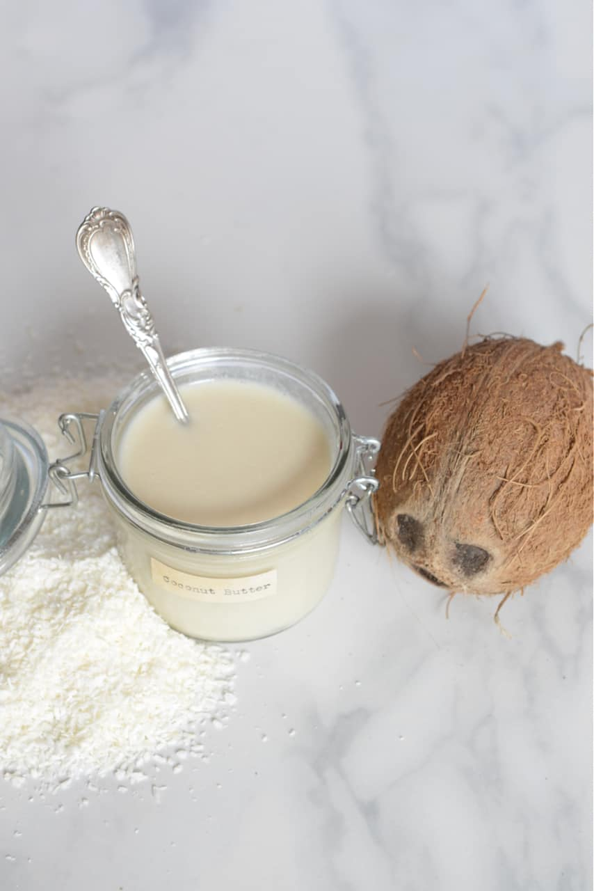Homemade coconut butter with a mature coconut on the side