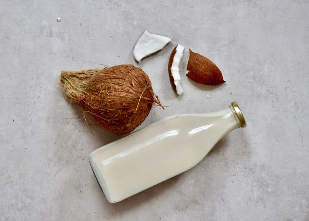 Coconut Milk in a glass bottle and a coconut next to it on a flat grey surface