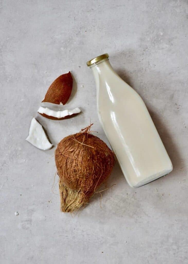 coconut milk bottle with mature coconut on the side and coconut meat