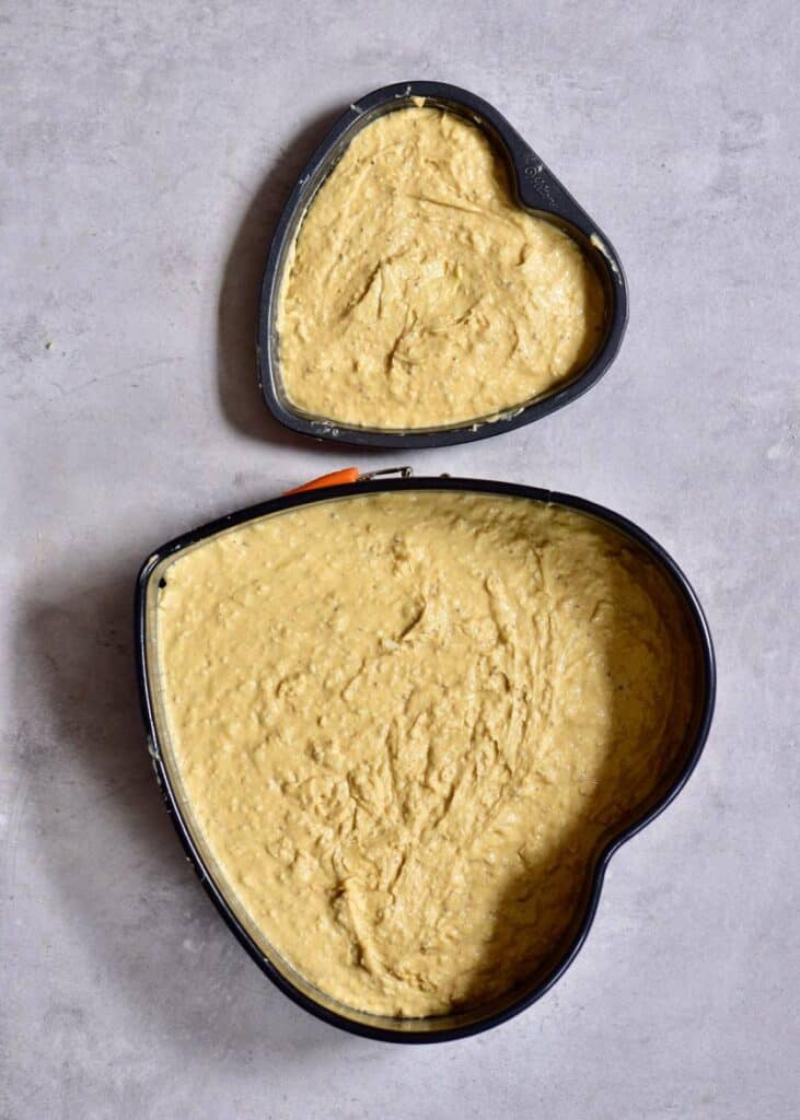 Cake batter in heart-shaped tins ready to bake