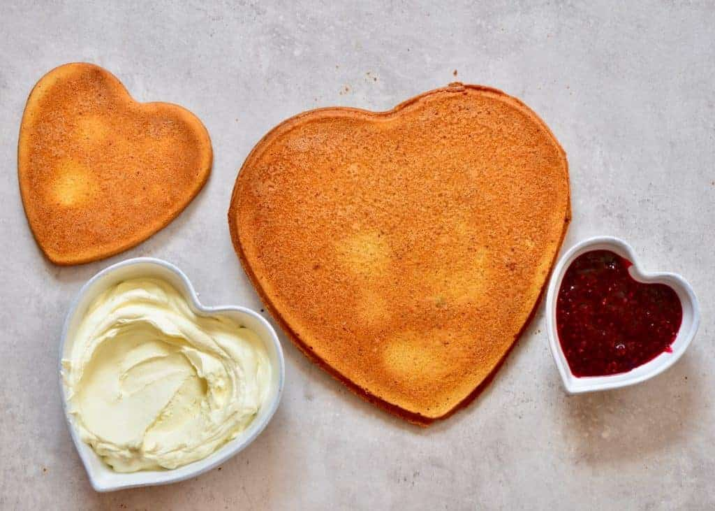 Heart shaped cake base ready to assemble with frosting and jam