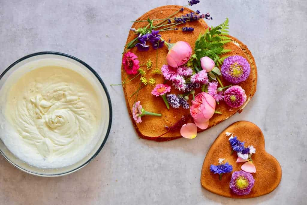 raspberry & coconut cake with whipped coconut cream frosting, and edible flowers to top