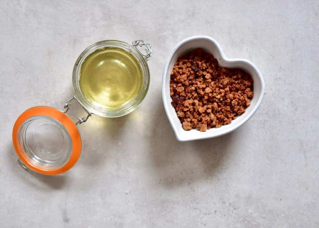 Coconut oil in a small jar and leftover coconut meal in a heart-shaped bowl