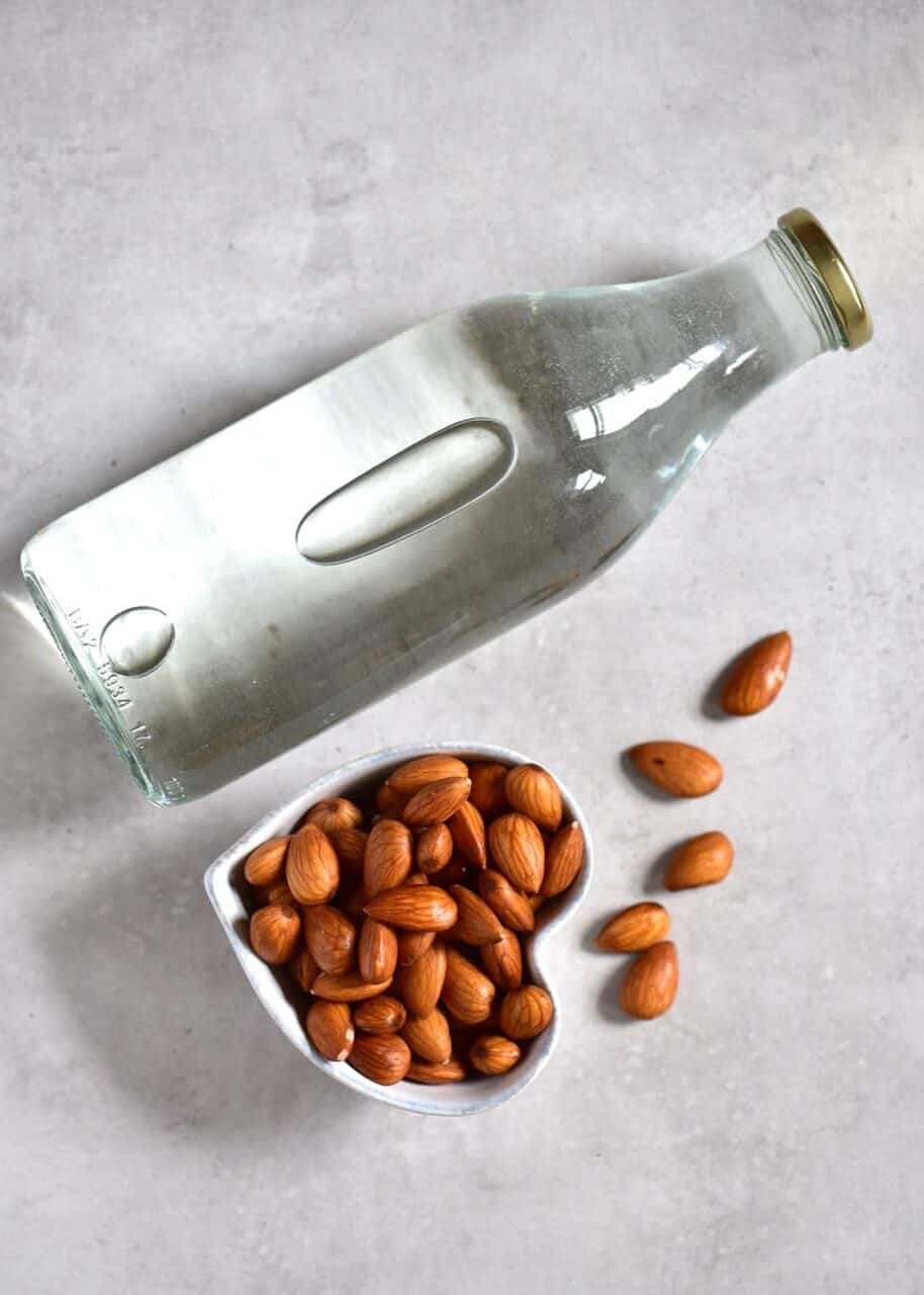 a bottle of water and a bowl with almonds