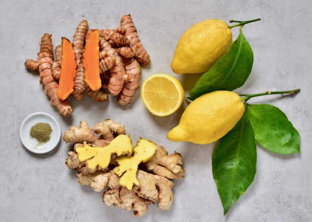 immune boosting ingredients including ginger, turmeric, pepper, and lemon on a grey board