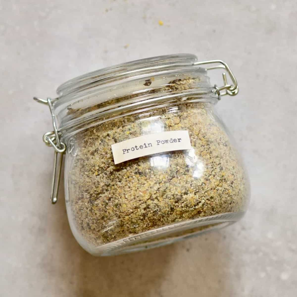 jar with homemade 5-seed vegan protein powder/ blend with hemp seeds, pumpkin seeds, linseed, sunflower seeds and pumpkin seeds. including the benefits of the various seeds