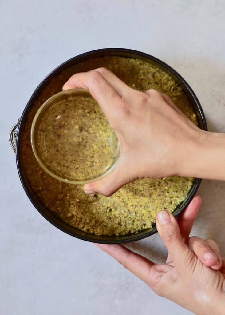 pressing vegan tart crust into tart tin with a glass
