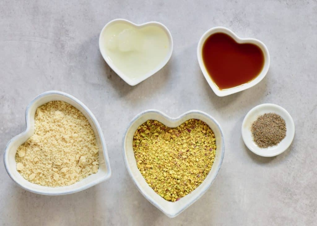 the ingredients for a raw vegan almond and pistachio tart crust