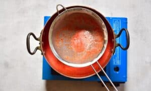 Sieving tomato juice into a pot