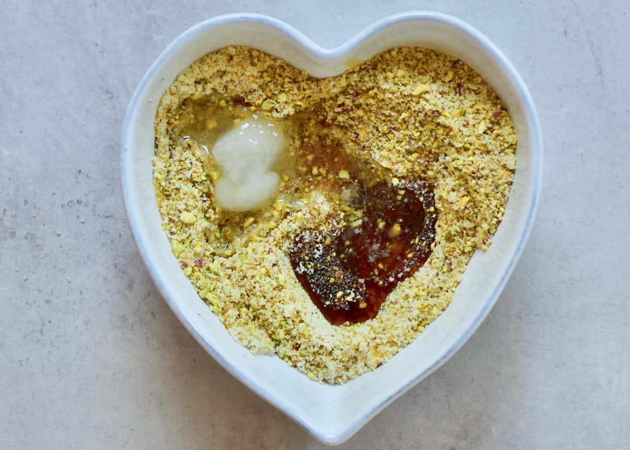 adding coconut oil and maple syrup to pistachio and almond raw vegan crust