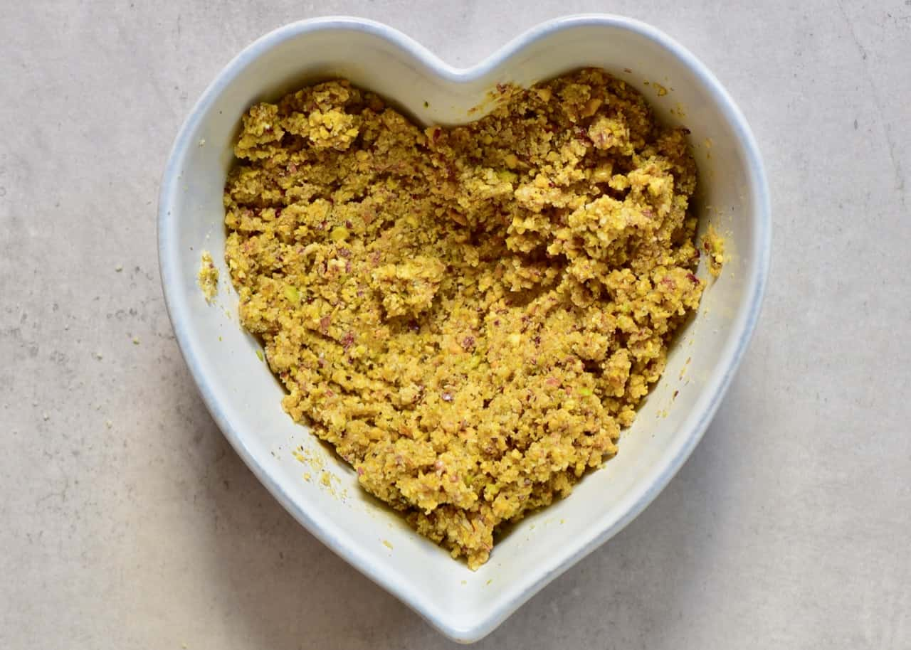 almond and pistachio raw vegan crust in a heart-shaped bowl