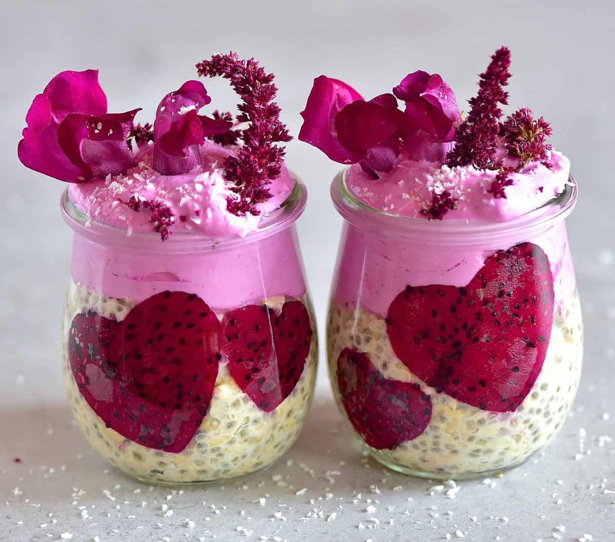 Two small jars with overnight oats pink dragon fruit yogurt pink dragonfruit hears and edible flowers as decoration