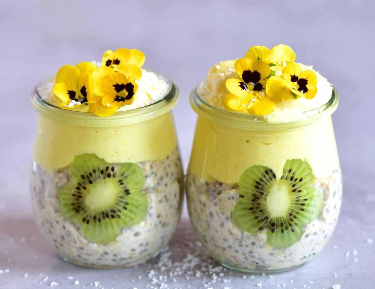 Two small jars with overnight oats mango yogurt and edible flowers as decoration